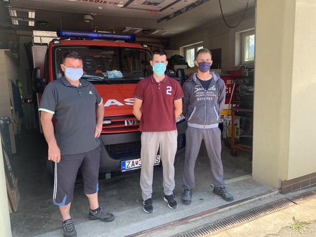 Veliteľ DHZ Trnové Roman Huliak (vpravo) a mladší technik Dominik Kuba s ďalším dobrovoľným hasičom pred garážou v urbárskom dome, kde skladujú techniku aj výstroj.